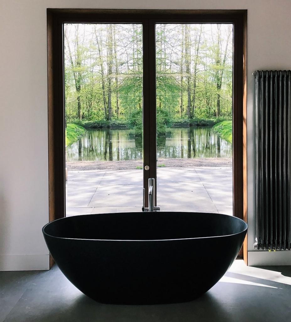 zwart vrijstaand bad van solid surface